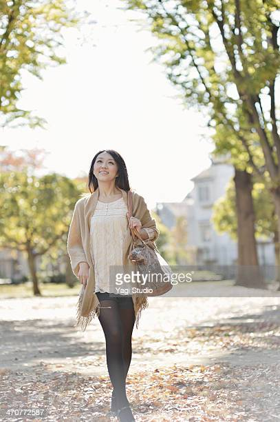 Smiling woman walking on park