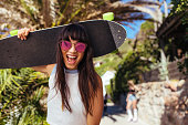 Smiling woman walking outdoors holding skateboard. Excited female with sunglasses and skateboard looking at camera and laughing.