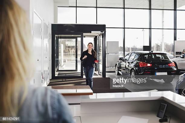 Smiling woman walking towards sales clerk at car showroom