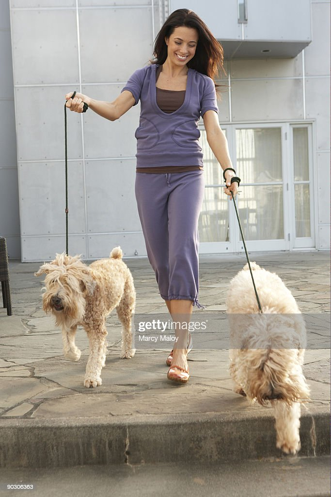 Smiling woman walking two dogs. : Stock Photo