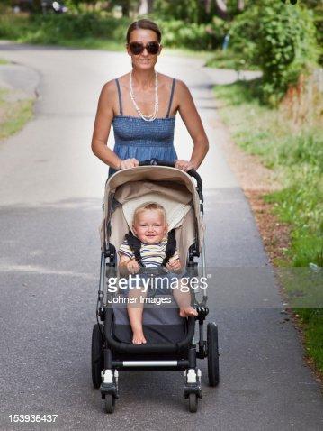 Smiling woman walking with son in pram