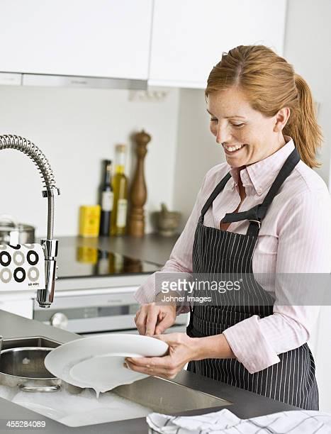 Smiling woman washing dishes