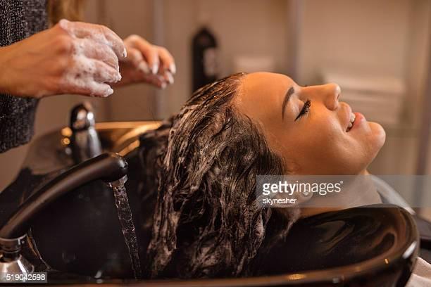 Smiling woman washing hair at hairdressers.