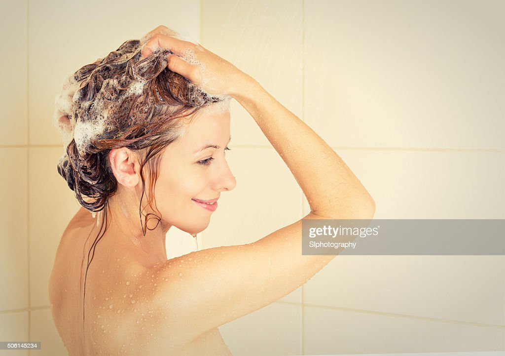 Smiling woman washing head with shampoo in shower : ストックフォト