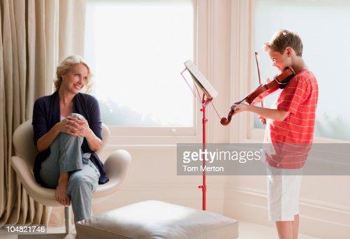 Smiling woman watching boy play violin : Foto de stock