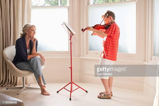 Smiling woman watching boy play violin