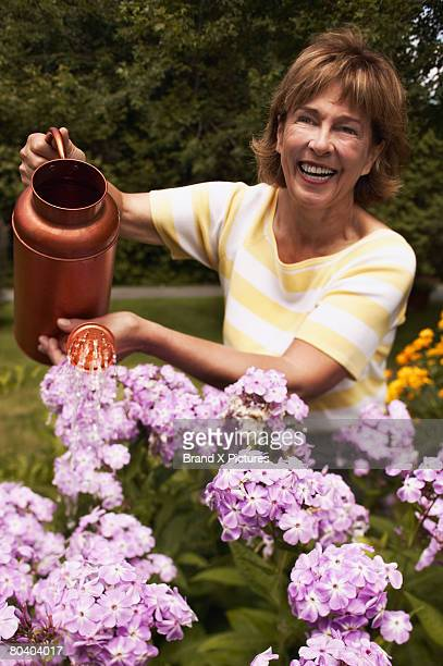 Smiling woman watering flowers