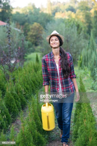 Smiling woman watering plants.
