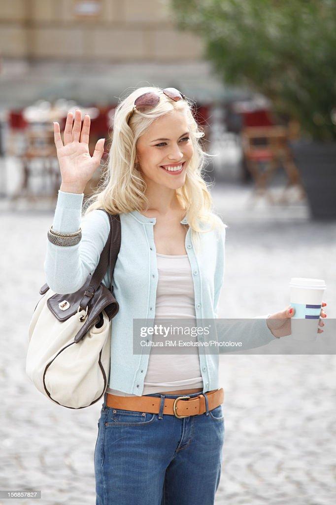 Smiling woman waving in courtyard