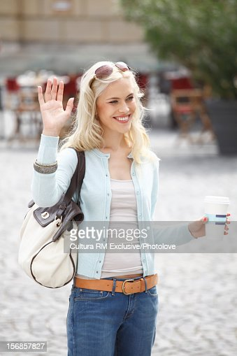 Smiling woman waving in courtyard