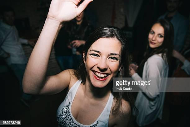 Smiling woman waving in nightclub