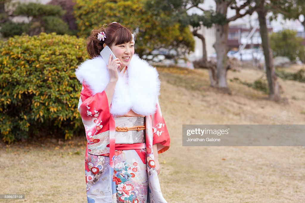 Smiling woman wearing a Kimono and using a phone : Stock Photo