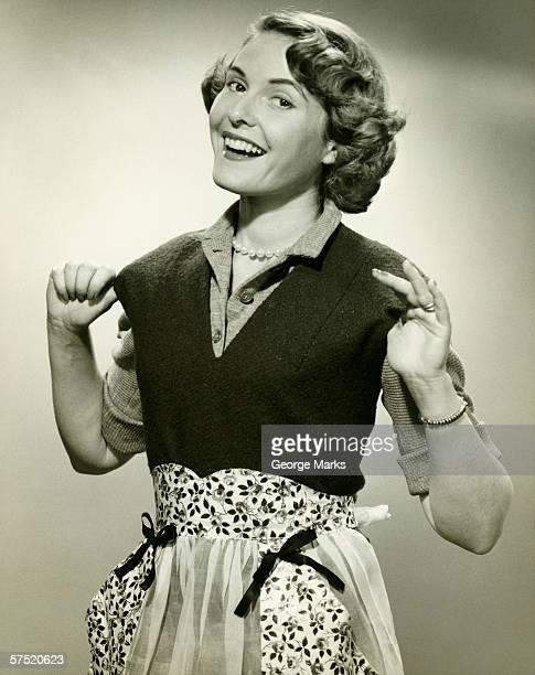 Smiling woman wearing apron posing in studio, (B&W), portrait
