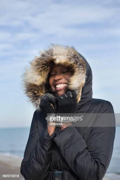 Smiling woman wearing coat on beach
