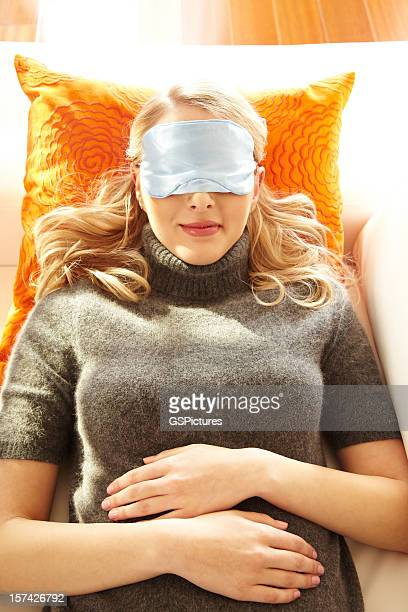 Smiling woman wearing eye pillow on couch