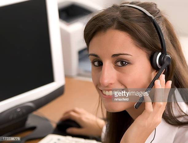 Smiling woman wearing headset in front of computer monitor