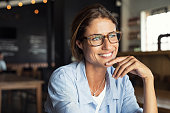 Portrait of beautiful mature woman sitting in cafeteria looking away. Cheerful mature woman wearing eyeglasses thinking with finger on chin. Happy woman relaxing at cafe and smiling.