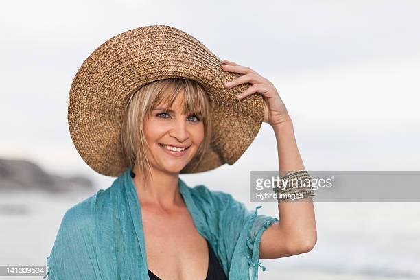 Femme souriante portant Chapeau de paille sur la plage