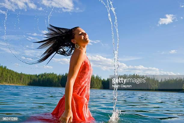 Smiling woman whipping hair in lake.
