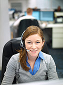 A smiling woman with a headset in an office