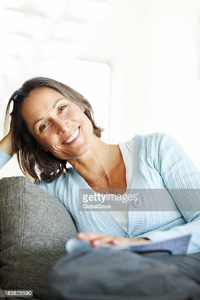 Smiling woman with a magazine sitting at home