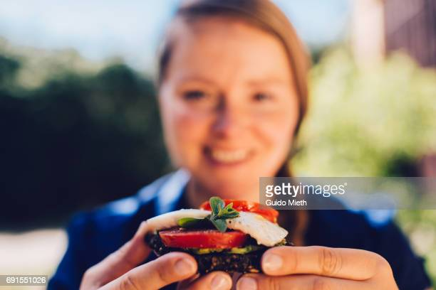Smiling woman with a sandwich.