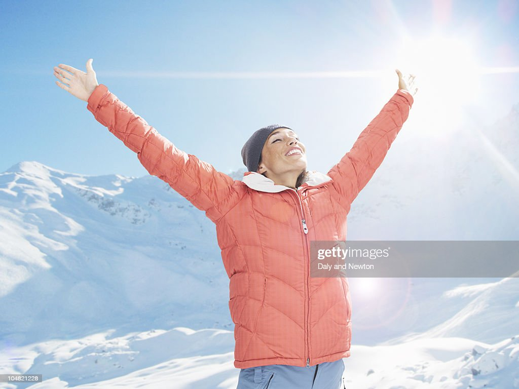 Smiling woman with arms outstretched on sunny, snowy mountain : Stock Photo