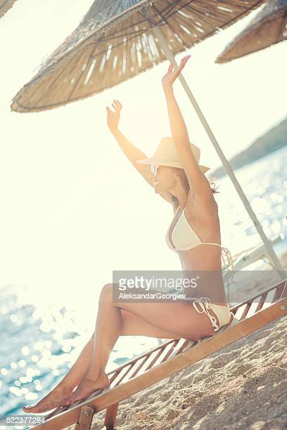Smiling Woman with Arms Raised to Sky Sunbathing on Beach