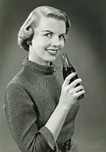 Smiling woman with bottle of Coca-Cola posing in studio, (B&W), portrait