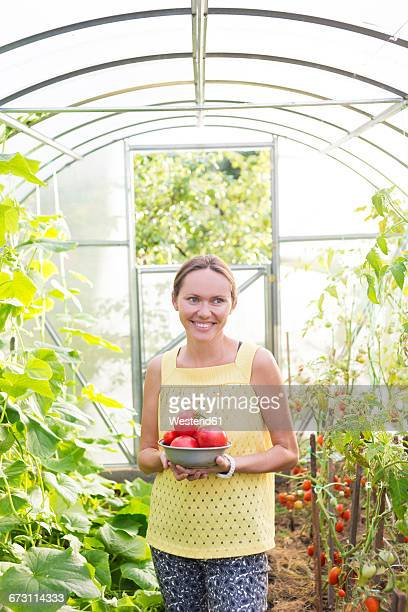 Smiling woman with bowl of harvested tomatoes in a greenhouse