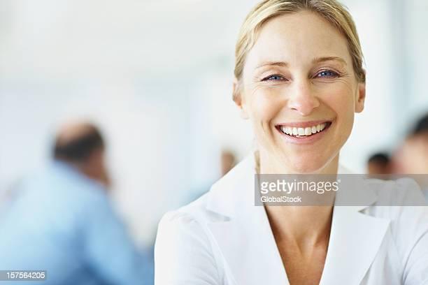 Mujer sonriente con colegas en la parte posterior