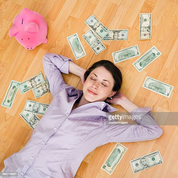 Smiling woman with cash and piggy bank