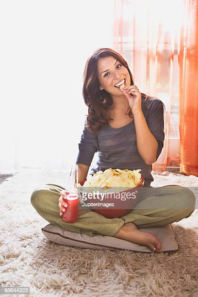 Smiling woman with chips and soda
