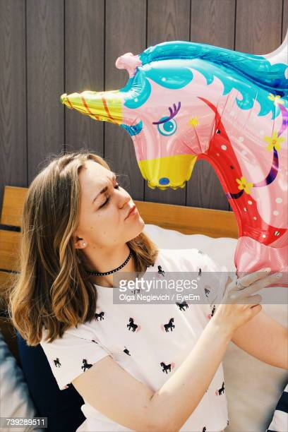 Smiling Woman With Closed Eyes Holding Unicorn Balloon Against Wall
