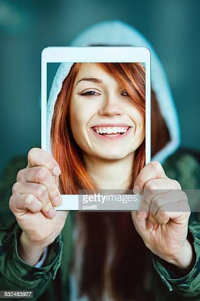 Femme souriante avec tablette numérique faire une autophoto
