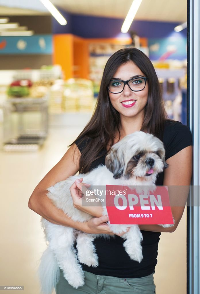 Smiling Woman with Dog on Entry of a Pet Shop