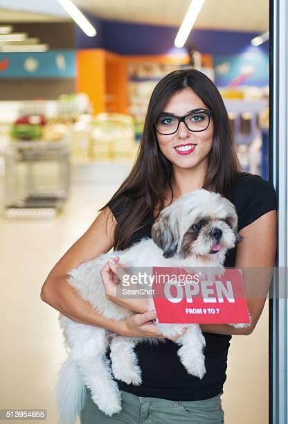 Mulher sorridente com Cão na entrada de Loja de Animais de Estimação