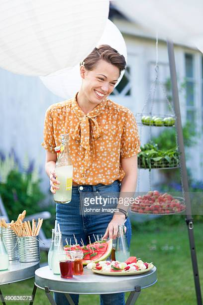 Smiling woman with drink at garden party