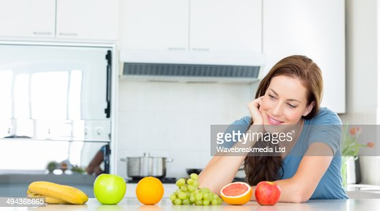 Smiling woman with fruits on counter in kitchen : Stock Photo