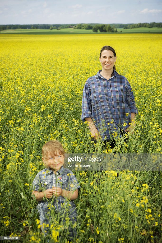 Smiling woman with girl on oilseed rape field : Stock Photo