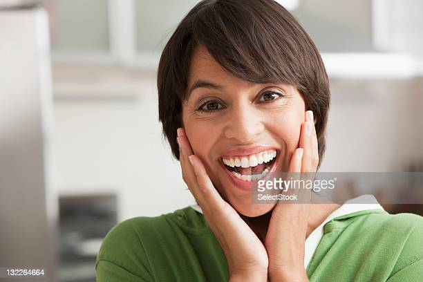 Smiling woman with hands pressed on cheeks