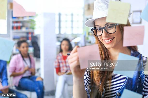 Smiling woman with hat and eyeglasses writing on post-it notes