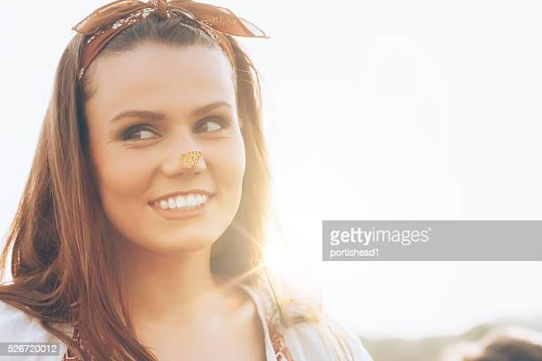 Smiling woman with headband having a butterfly on her nose