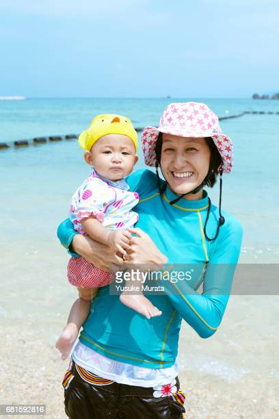 Smiling woman with her baby on beach