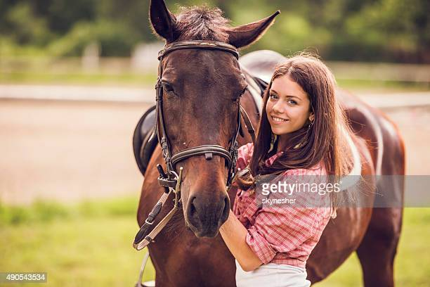 Smiling woman with her horse outdoors looking at camera.
