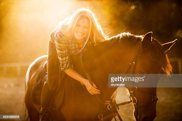 Smiling woman with horse at sunset.