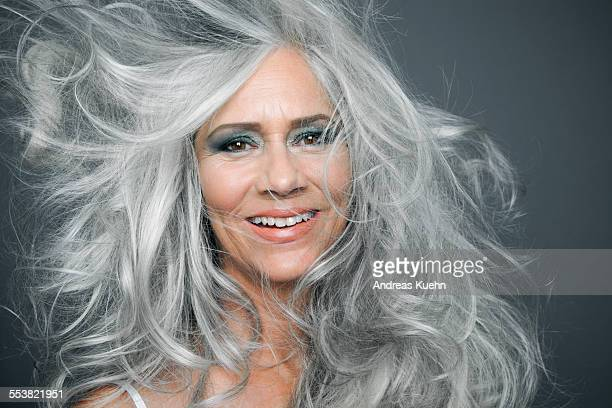 Smiling woman with long, grey hair blowing.