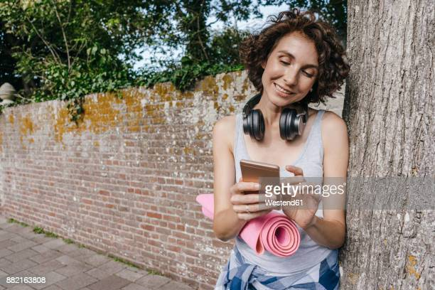 Smiling woman with mat, headphones and cell phone on pavement