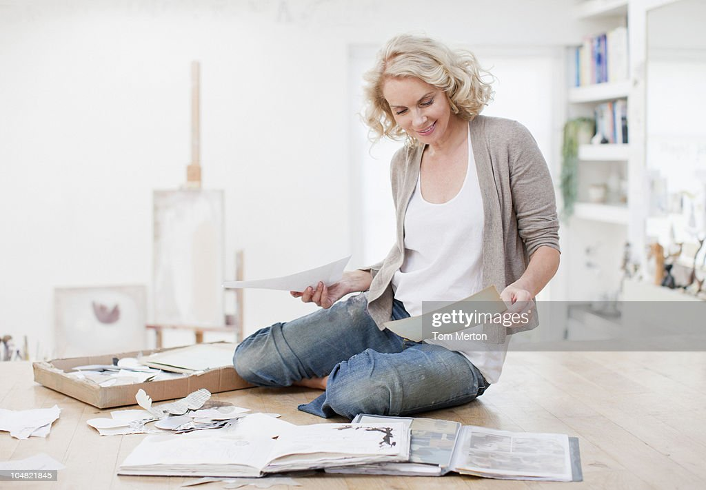 Smiling woman with photograph album and scrapbook : Stock Photo