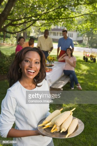 Smiling woman with plate of corn at picnic : Stock Photo